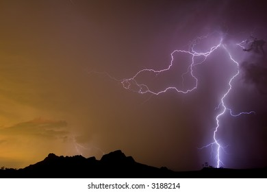 Desert lightning with storm picking up glow of city lights