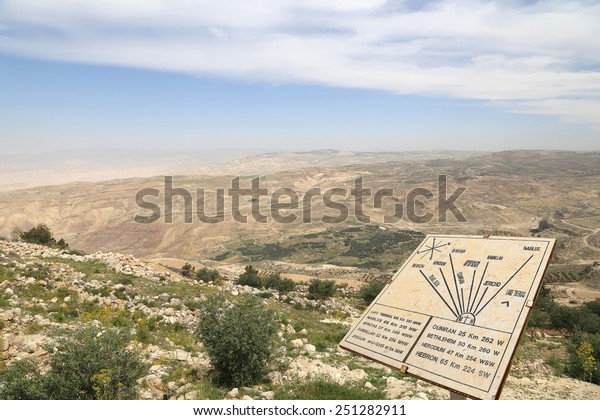 desert mountain landscape (aerial view from Mount Nebo) and plaque showing the distance from Mount Nebo to various locations, Jordan, Middle East