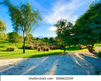 desert oasis mountain scene featuring lush green trees and bright blue sky with mountains in the distance as well as deep shadows and bright sun rays in a golf course or resort setting