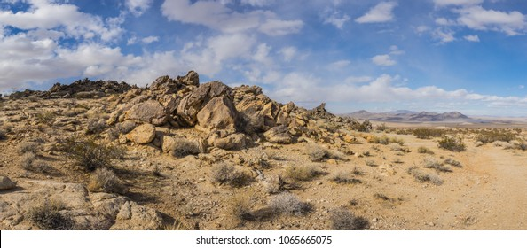 Desert panorama shows dirt trail and boulder rock pile in southern California.