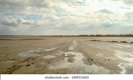 Desert parched estuary. In the rare puddles reflected the clouds. In the sky clouds.   A flat horizon line is far in sight. Desert.  Only wet sand under the sky. Nobody.