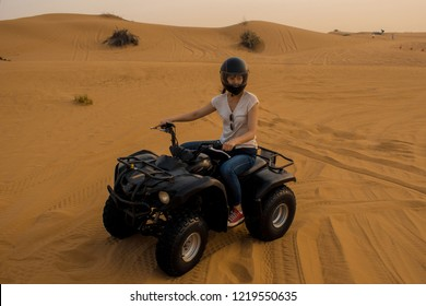 desert Quad Biking. Young girl in a helmet driving a Quad bike