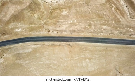 Desert road - Aerial image of a new two lane road surrounded by dry desert landscape