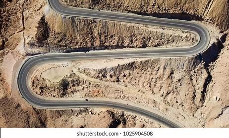砂漠の道 – 蛇紋岩の山道を行き来する交通の航空画像