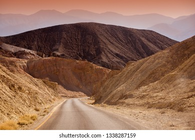 Desert road leading to a canyon of Death Valley national park, USA