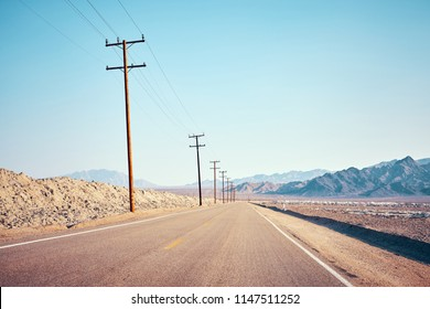 Desert road with wooden electricity posts, color toned picture, USA.