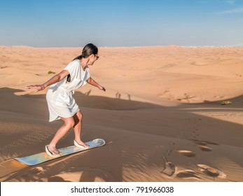 Desert safari near Dubai, UAE,  Young woman sand boarding in the desert over the sand dunes