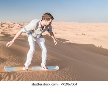 Desert safari near Dubai, UAE,  Young man sand boarding over the dunes of the Dubai desert