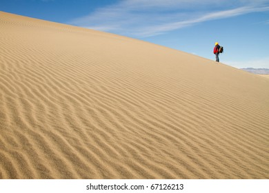 Desert Sand Dune with a Lone Hiker in the Distance.