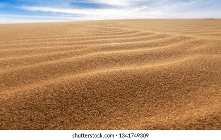 Desert sand dunes and sand grains spread in the sky with strong winds, White sand dunes in Mui Ne, Vietnam.