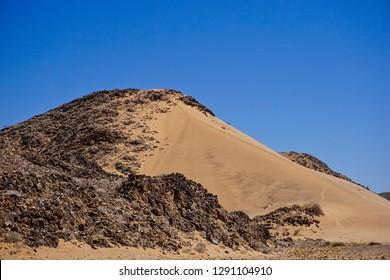 Desert sands enveloping rocky granite hills, Damaraland, Namibia, Africa.