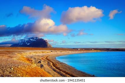 Desert scenery - Istfjorden beach, blue water of Greenland sea, severe tundra land, lonely black rock against the background of beautiful sky near Barentsburg, Svalbard (Spitsbergen island), Norway