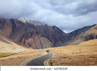 Desert scenic view of high mountain winding road and a car against the background of rugged mountain wall and dramatic cloudy sky in Pangong range, Ladakh, Himalaya, Jammu & Kashmir, Northern India