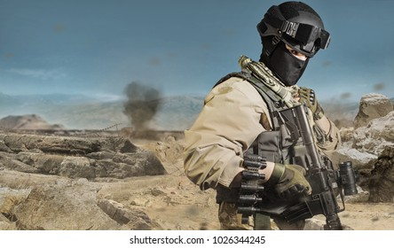 Desert soldier. Photo of a fully equipped military soldier standing with rifle, ammo on desert battlefield background.