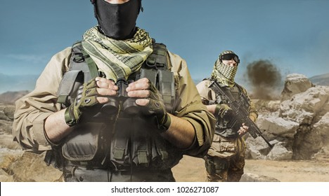 Desert soldiers. Photo of a fully equipped soldiers posing on a desert battlefield background.