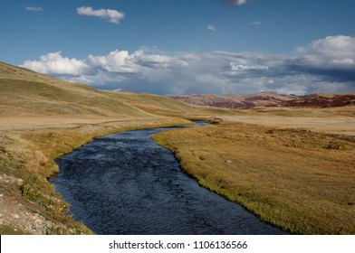 Desert steppe river valley on a highland mountain plateau with ranges of hills on a horizon storm skyline