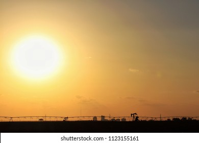 Desert sun and Permian basin silhouettes
