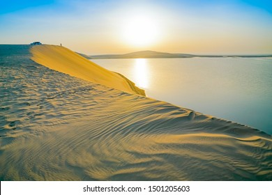 Desert at sunrise, morning glow over dunes and inland sea of the Sealine Desert just out of Doha, Qatar.