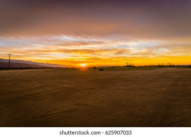 Desert sunrise over an empty dirt parking lot with mountains and telephone poles in the background.