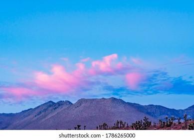 Desert sunset with barren mountains under pink Clora day blue skies.