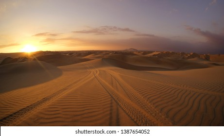 Desert at sunset hour with dune buggy tires tracks in the sand in the foreground. Buggy tour in Huacachina, Ica, Peru. Extreme sports, adventure and travel concept. Wide angle shot.