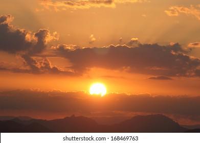 Desert sunset over hills on horizon
