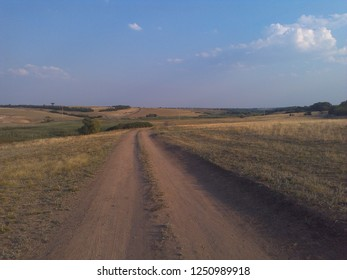 desert terrain, two ruts of the road through mountainous nature, meadows, uncultivated fields, natural nature, unplanted fields, fine grass of a spring day