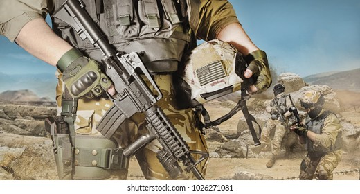 Desert war soldiers. Photo of a fully equipped soldiers posing with guns and rifles on a desert battlefield background.