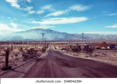 Deserted abandoned empty road in San Felipe, Mexico, South California, mountain peak in distance with blue sunny sky with few white clouds, dirty wide road and several empty houses, no people or cars