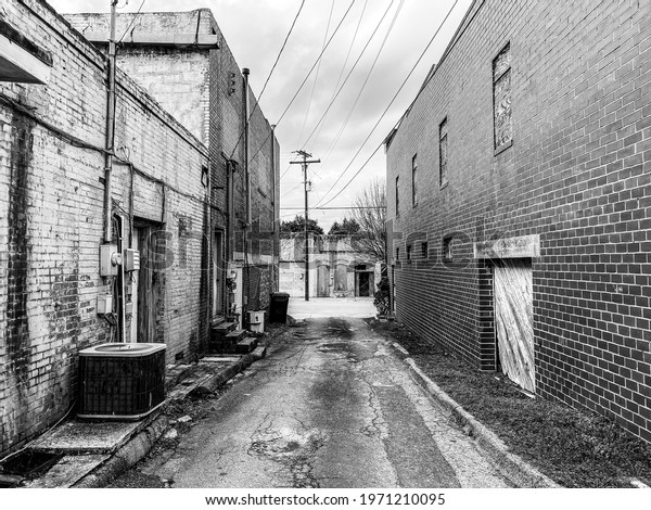 deserted abandoned rural town back alley in dark lonely moody despair black and white as an architecture scene