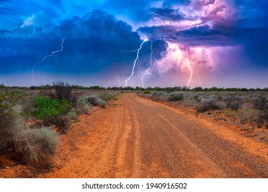 Deserted Australian outback landscape with red dirt road towards horizon with bushes in roadsides and heavy thunderstorm with white purple lightnings on the horizon