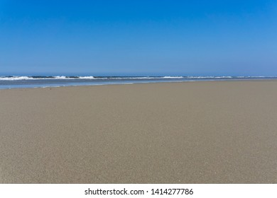Deserted beach with blue sky and sunshine on the Danish island of Romo