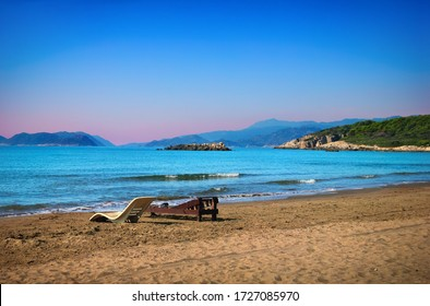Deserted beach with empty sun beds in the absence of people, sand, clear blue water, distant islands and morning sky. Beautiful nature scenery in Andriake beach, Demre, Antalya province, Turkey