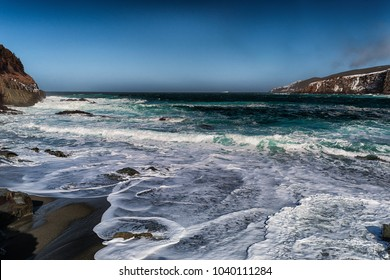 A deserted beach with lots of foamy white waves rolling over sand and rocks.The cove has shorelines with snow and ice on a cold sunny day. The sky is a rich blue and the ocean is a deep coral green.