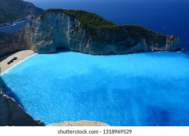 A deserted beach with a rusting ship surrounded by cliffs and blue water of the Ionian sea on a warm sunny day. View from the top of the rock. Navagio Bay, Zakynthos island, Ionian Islands, Greece.