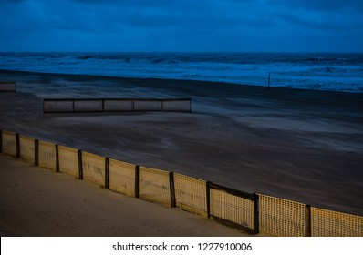 Deserted beach with some fences at dusk at the Flemish North Sea, Blankenberge, Flanders / Belgium