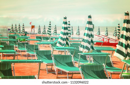 Deserted beach with sunbeds and umbrellas at the Italian Adriatic coast near Rimini and Riccione in the preseason, Italy
