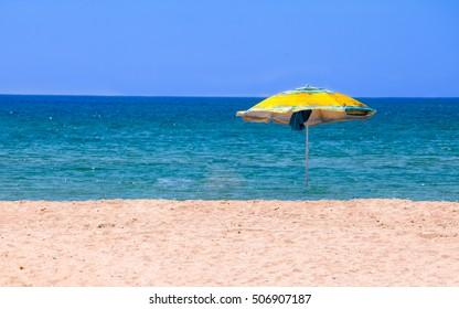 Deserted beach with umbrella