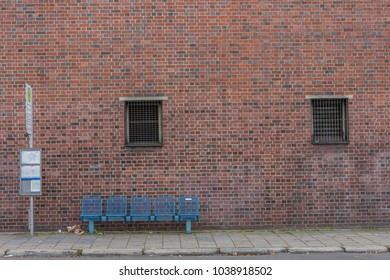 A deserted bus stop with a blue bench in front of a weathered industrial red brick wall with two barred windows.