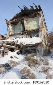 Deserted and a demolished old brick house in the winter city against a blue sky