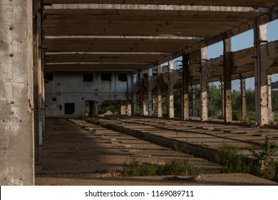 A deserted industrial plant site with old deserted structure on a beautiful sunset.