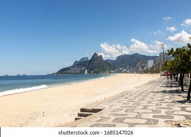Deserted Ipanema and Leblon beach with the Two Brothers mountain in the background during the COVID-19 Corona virus outbreak on a sunny midday in Rio de Janeiro, Brazil