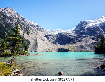 deserted landscape with amazing turquoise milky transparent waters of joffre lake in the middle of a pines trees forest and a steep summit covered of snow during a sunny day