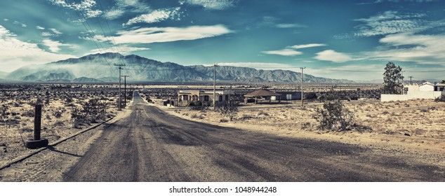 Deserted lonely empty road in San Felipe, Mexico, distant mountain with white summer clouds, few abandoned empty houses in the scorching heat, no cars or people, super wide panorama stitch, Covid-19