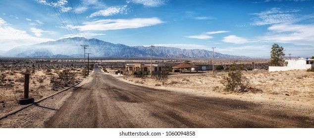 Deserted lonely empty road in San Felipe, Mexico, distant mountain with white summer clouds, few abandoned empty houses in the scorching heat, no cars or people, super wide panorama stitch