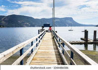 Deserted Narrow Wooden Jetty on a Summer Morning. Maple Bay, Vancouver Island, BC, Canada.