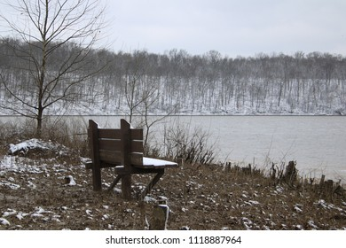 Deserted park bench in snowy park with lake in background