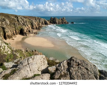 Deserted Pedn Vounder beach and Logan Rock headland as seen from South Cornwall Coastal path near Porthcurno, Cornwall, England, UK
