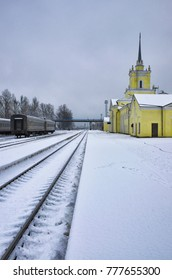 Deserted platform and railway station in the winter evening. City of Dno, Pskov Oblast, Russia