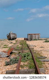 Deserted railway track, derelict house and boat on beach at Dungeness in Kent, England